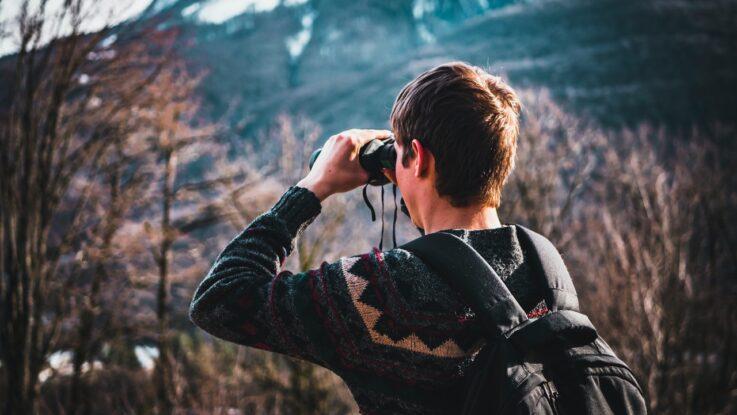 Person kigger i kikkert ud over natur