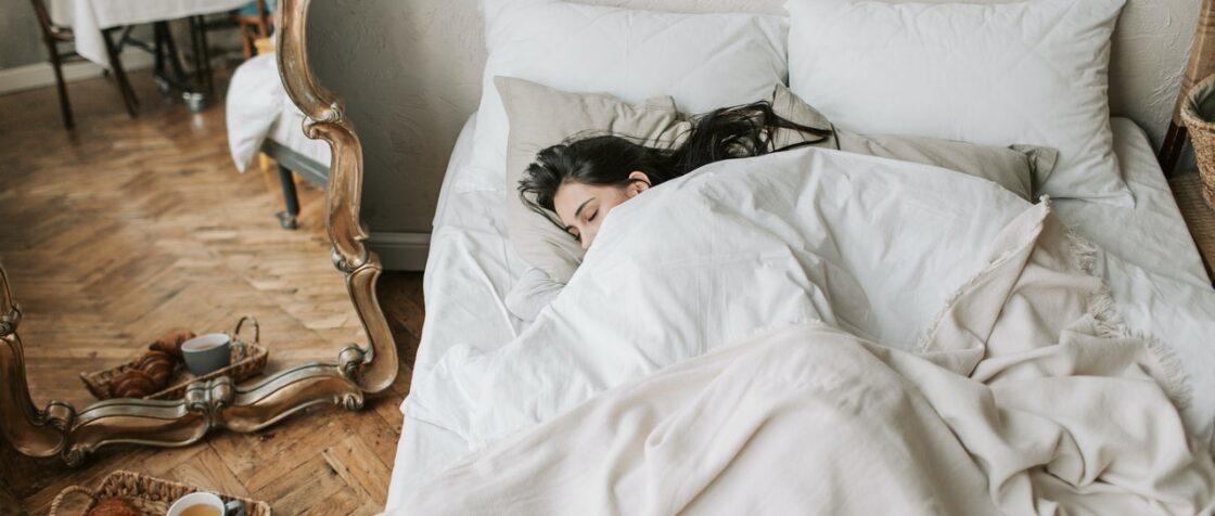 Kvinde sover i seng på soveværelse